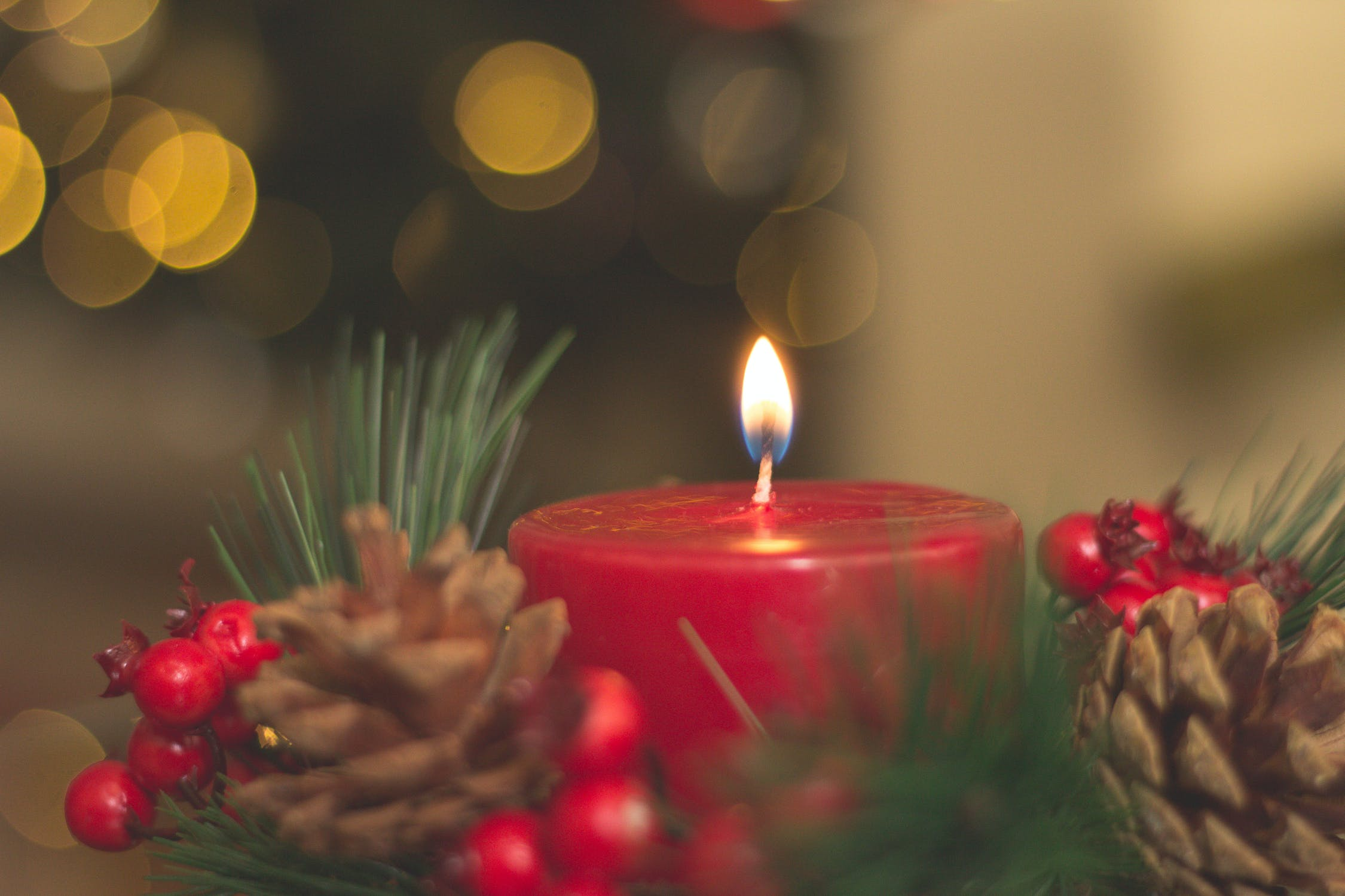 Lit candle surrounded by pinecones, greenery, and winter berries