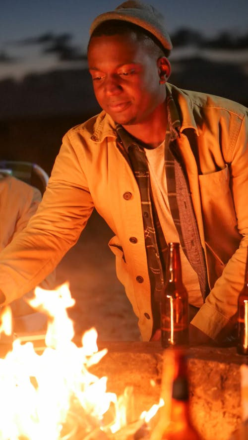 Man Leaning in front of a Fire Pit