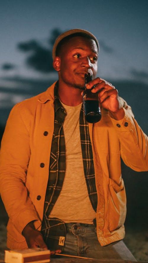 Man in Brown Jacket Drinking a Beer