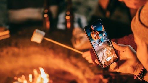 Man Recording on His Smartphone Women Roasting Marshmallow