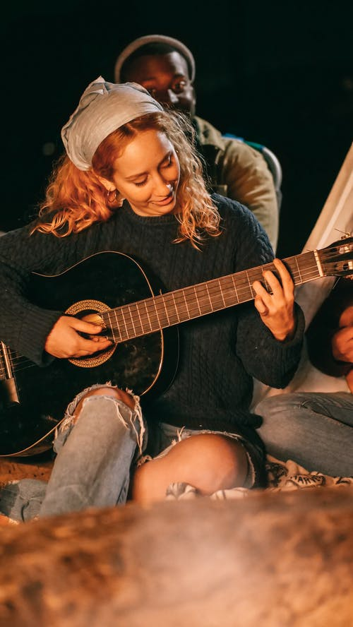 Woman in Black Long Sleeve Shirt Playing Acoustic Guitar