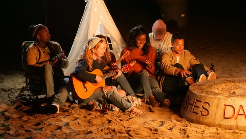 Group of People Sitting on Brown Sand during Nighttime