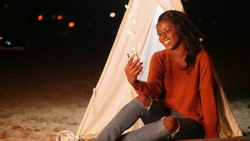 Woman Leaning on a White Teepee Taking a Selfie
