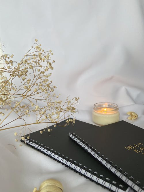 Notebooks placed on white cloth with flower and burning candle