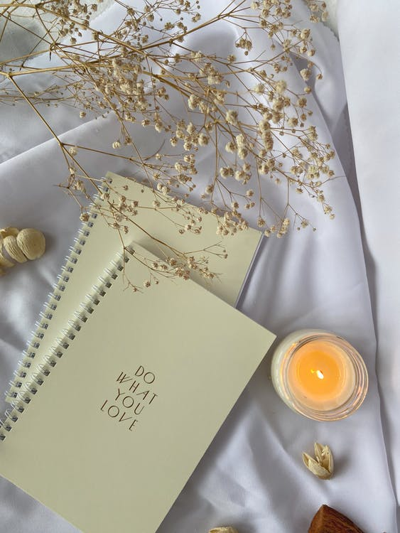 Top view composition of white spiral copybooks with inscription Do What You Want placed on white cloth with burning candle and tender flower