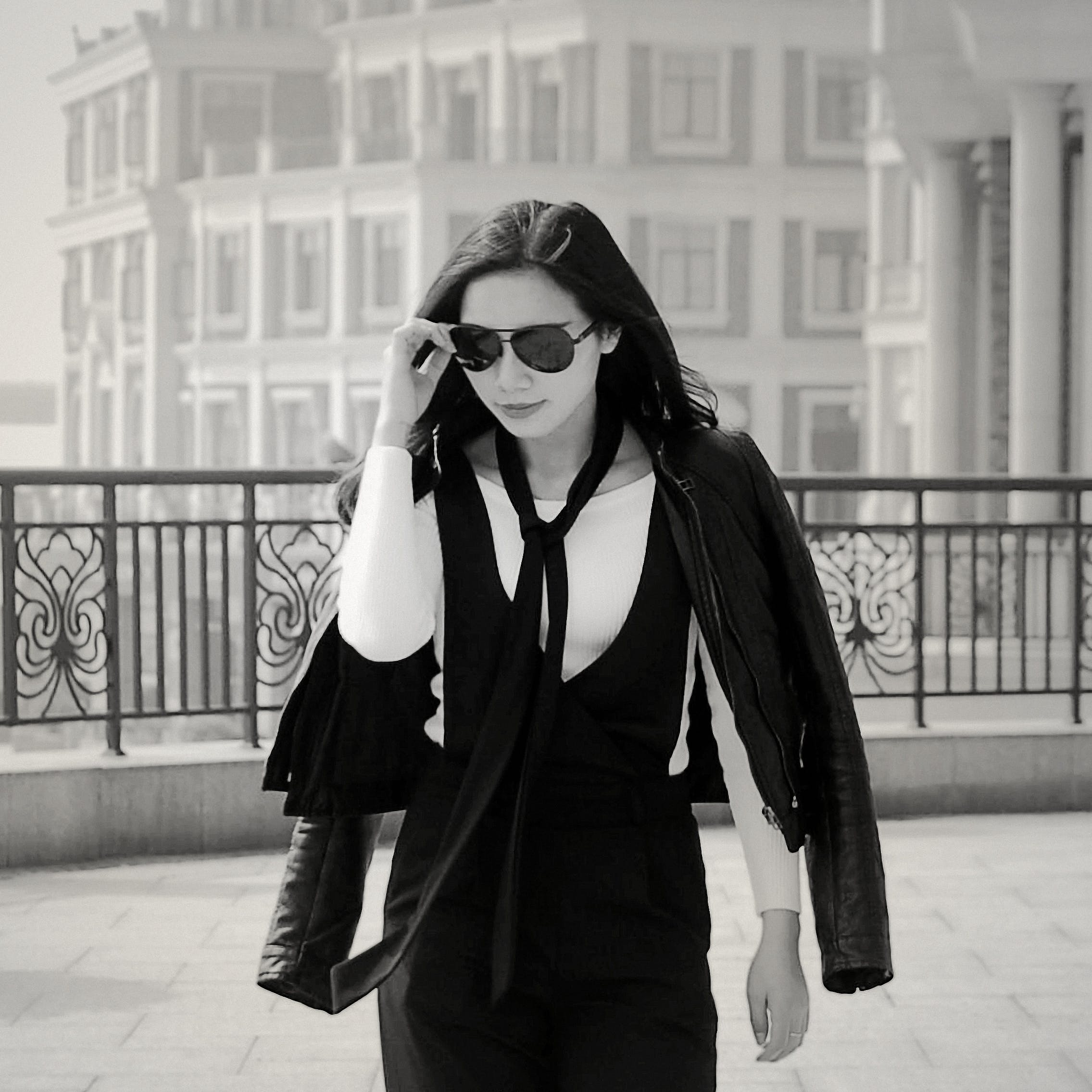 Greyscale Photo of Woman Wearing Sunglasses Long Sleeves Shirt and Skirt during Daytime
