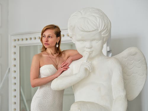 Thoughtful woman leaning on white sculpture of angel