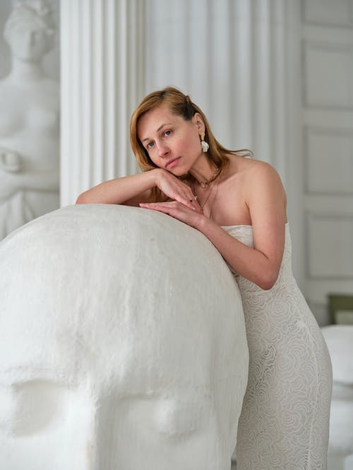 Gentle dreamy woman leaning on white sculpture