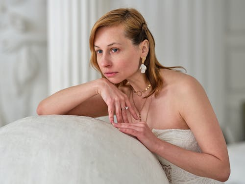 Dreamy alluring woman in white dress pondering