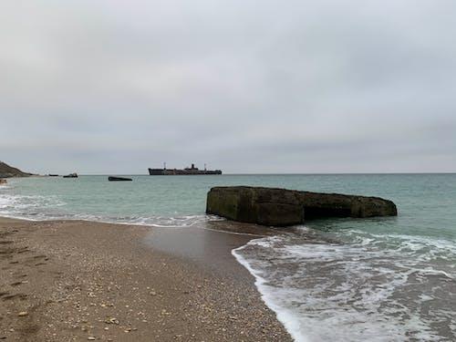 Dark ship in calm sea under cloudy sky