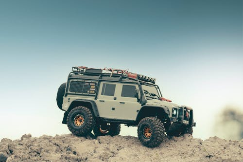 Modern off roader car parked on rough rocky terrain under blue sky in nature