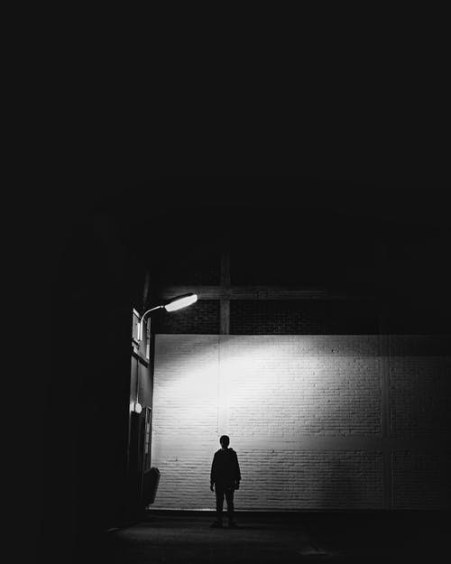 Silhouette Of Man Standing Under Lamp Post
