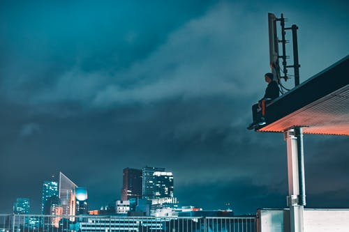 Man Sitting on Building Atop