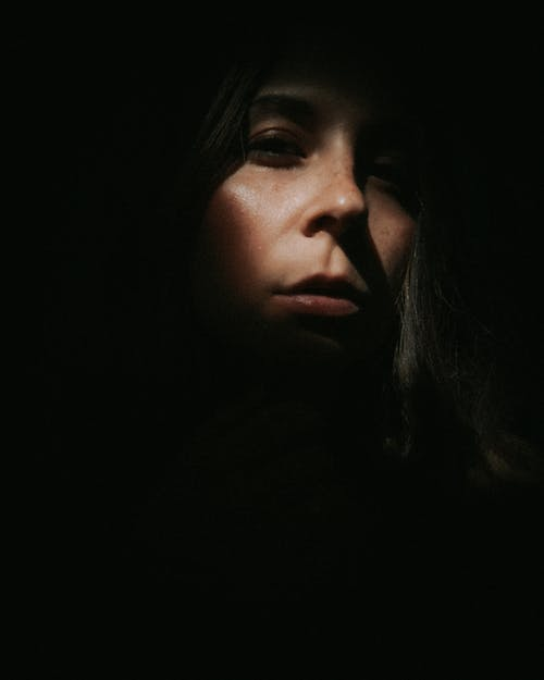 Anonymous enigmatic woman standing in darkness