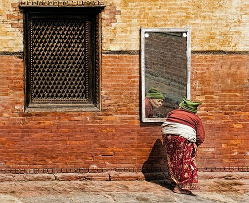 An Old Woman Looking at a Mirror