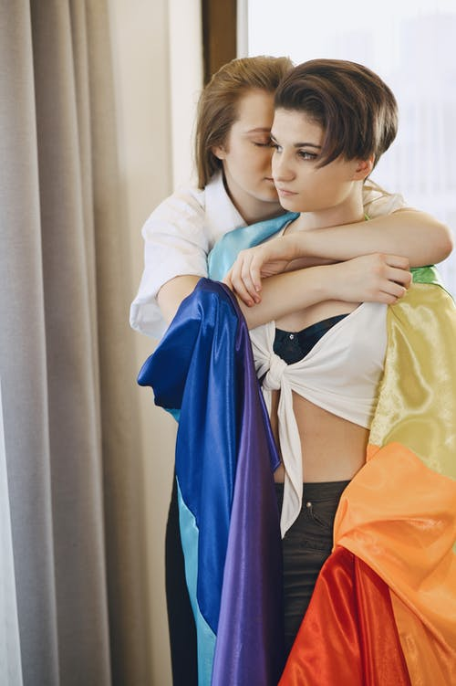 A Woman Hugging Her Partner Draped with the Rainbow Flag