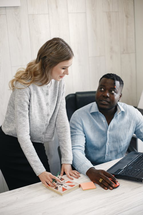 Man Sitting Looking at Woman Standing Beside Him