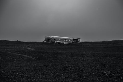 Grayscale Photo of White Bus on the Field
