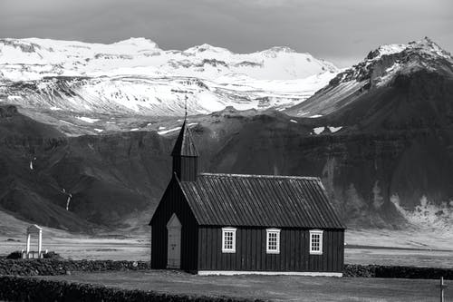 Grayscale Photo of Wooden House Near Mountain