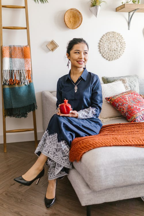 Smiling Woman Sitting On Sofa With A Candle