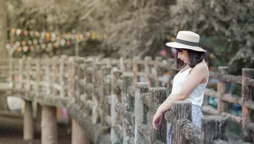 Woman Wearing White Tank Top and White Hat Standing on a Boardwalk