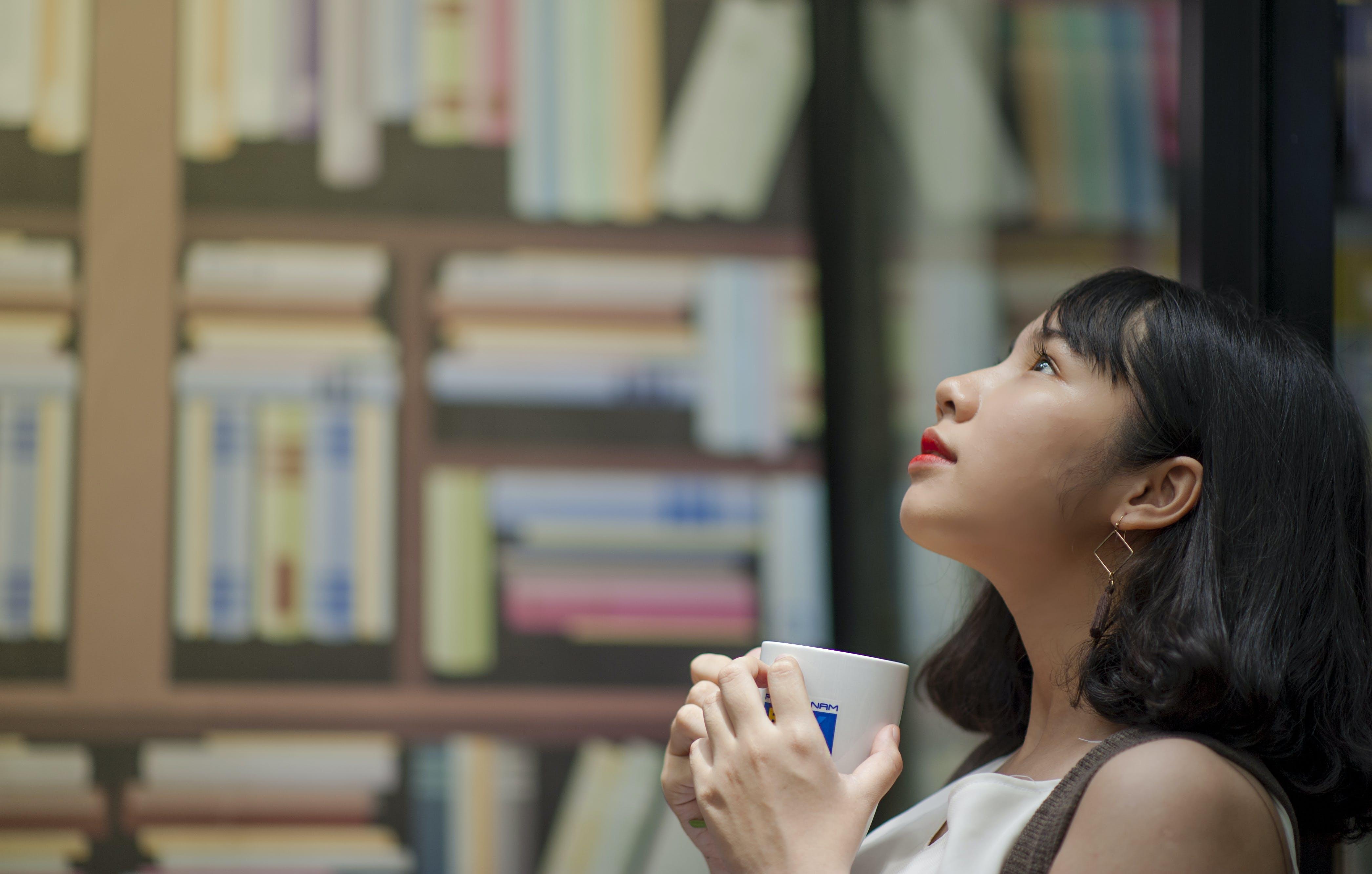 Woman Wearing White Shirt Looking on Top Holding White Ceramic Mug