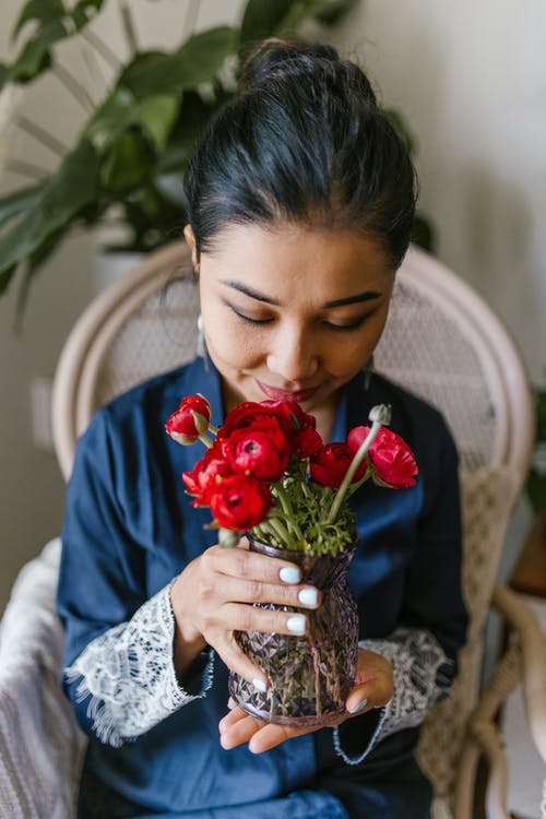 Woman Smelling A Bunch Of Red Flowers