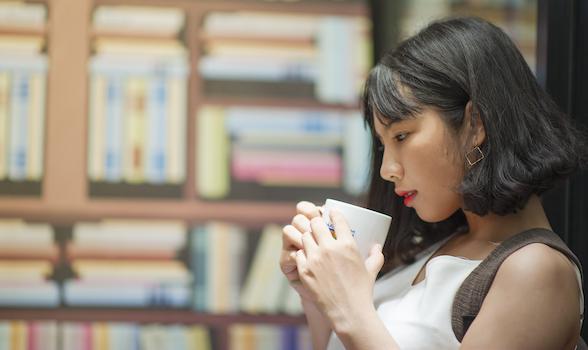 Photography of A Woman Holding White Coffee Mug
