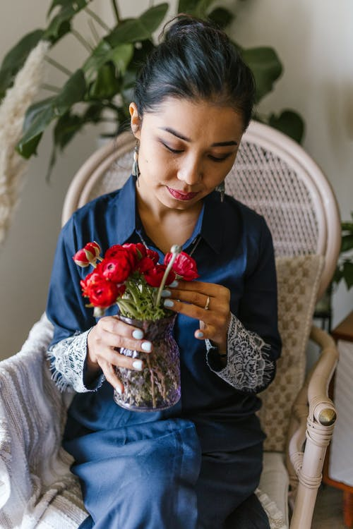 Woman Holding Red Flowers In A Vase