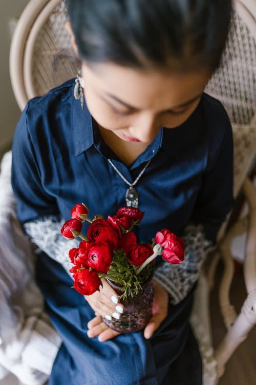 Woman Holding A Glass Vase With Red Flowers