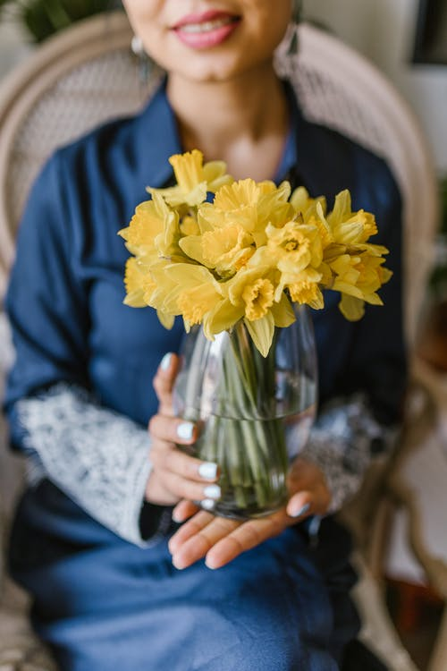 Crop Photo Of Woman Holding A Vase Of Yellow Flowers