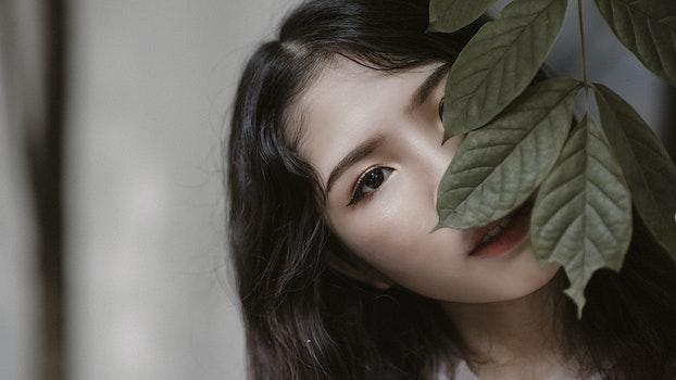 Woman With Black Hair Peeking Through Green Leaves