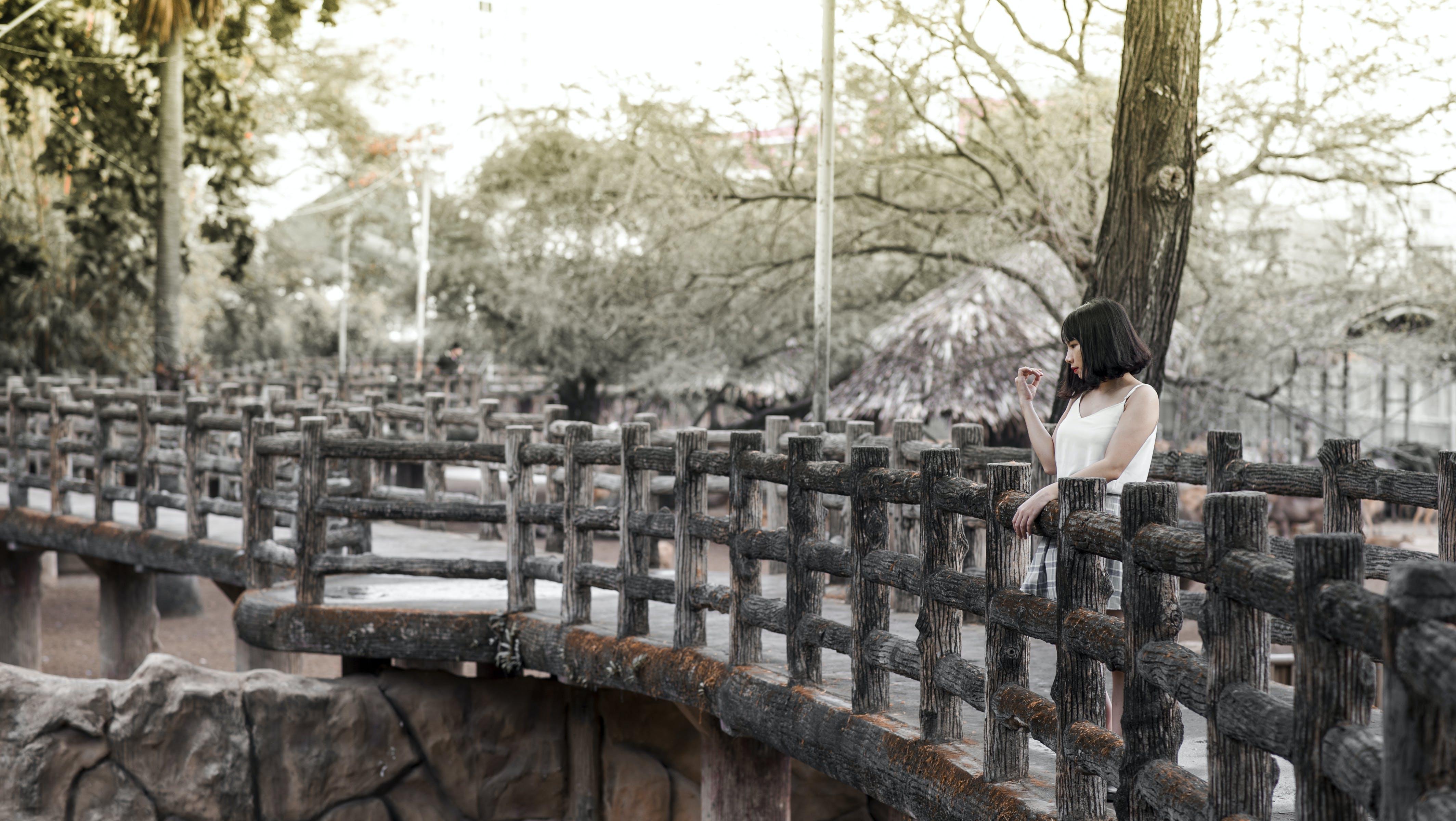 Woman in White Shirt Standing on Black Bridge