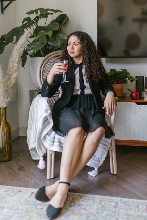 Woman Sitting On A Chair With A Glass Of Wine