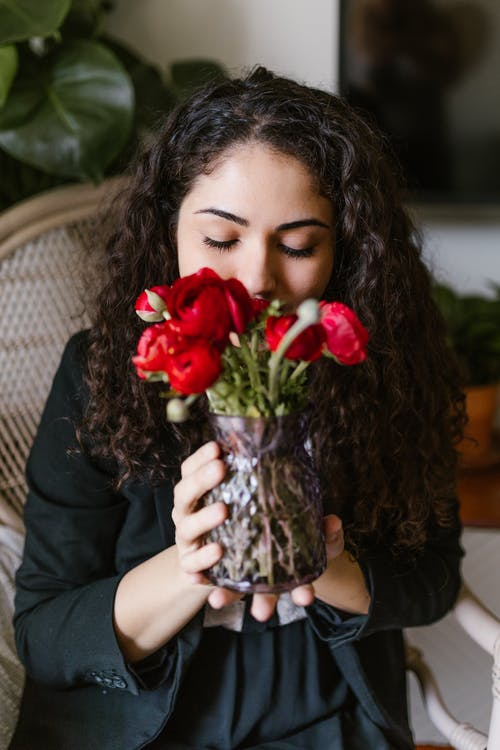 Woman Smelling Red Flowers In A Vase