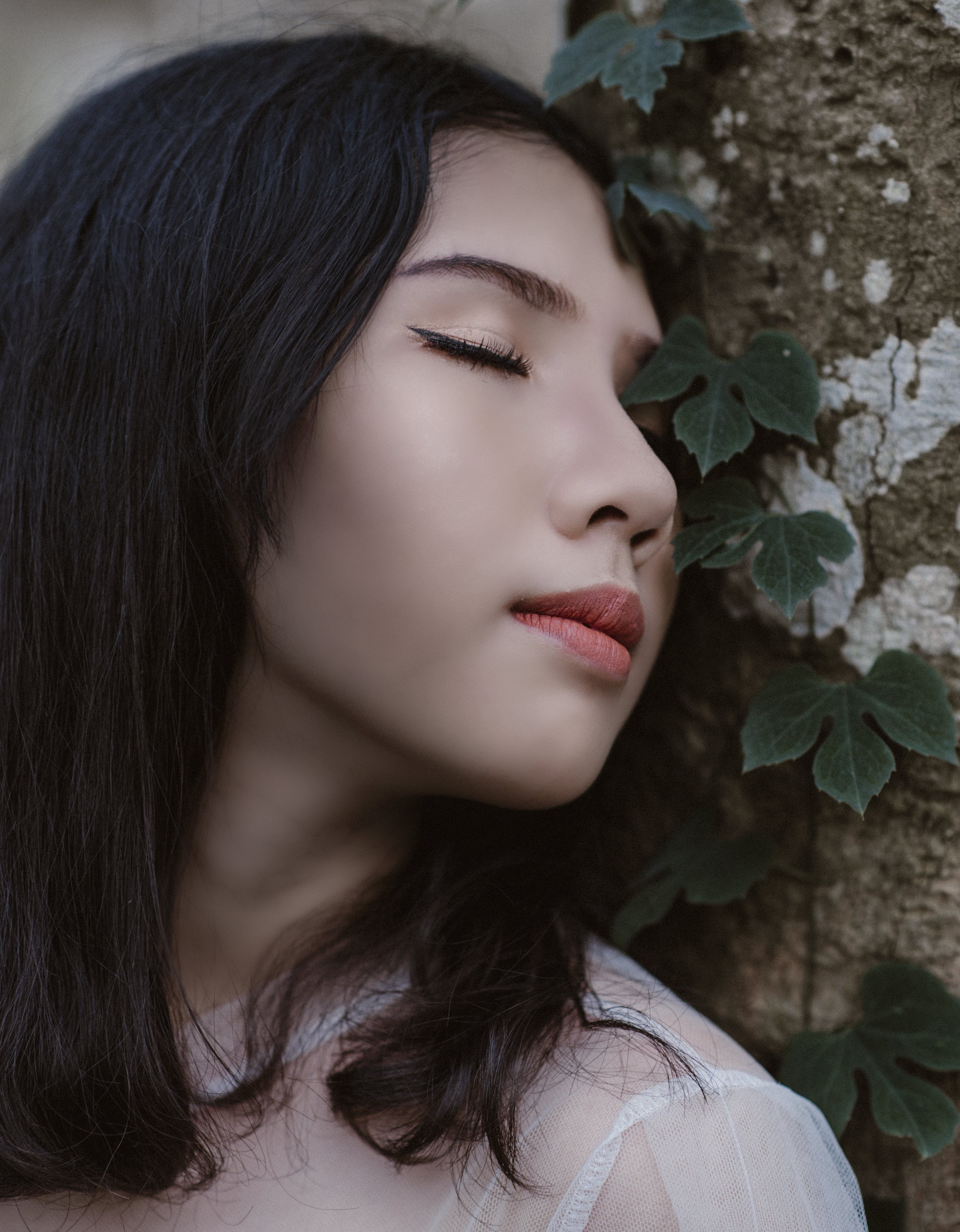 Woman Closing Her Eyes Beside Green Vine Plant