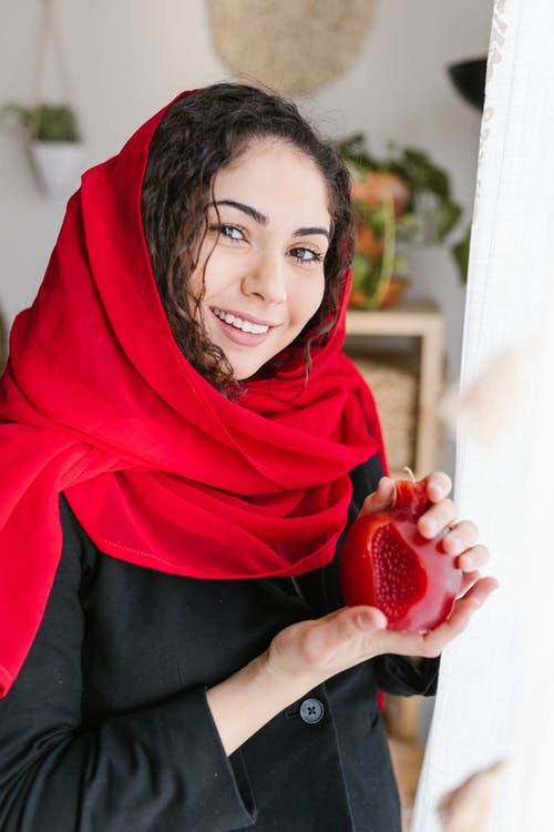 Woman in Red Hijab Holding Red Candle