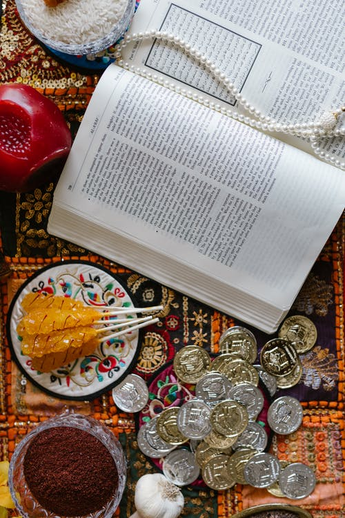 Silver Round Coins Beside An Open White Book Page