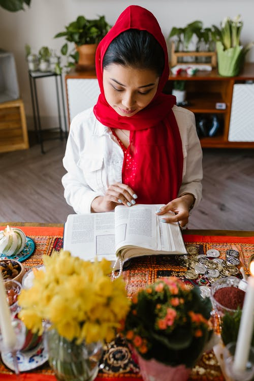 Woman in White Long Sleeve Shirt Reading A Book