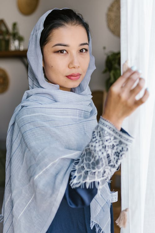 Woman With Blue Hijab Standing Near A Curtain