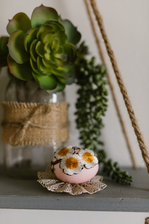 Decorated Egg On Table Beside A Succelent Plant