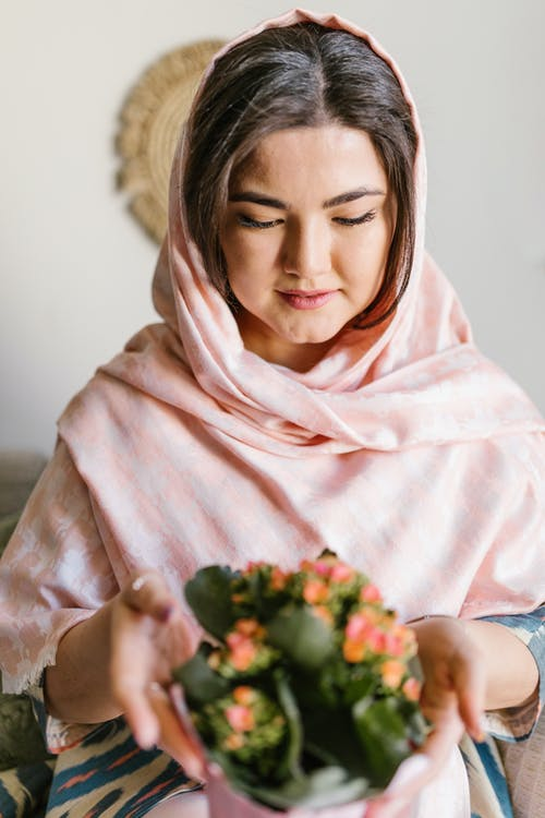 Woman In Pink Veil Holding A Bunch Of Flowers