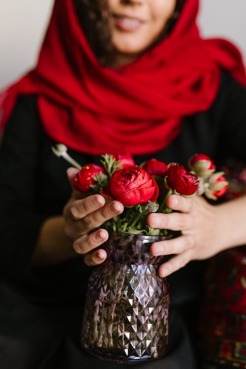 Crop Photo Of Woman Holding A Vase With Red Flowers