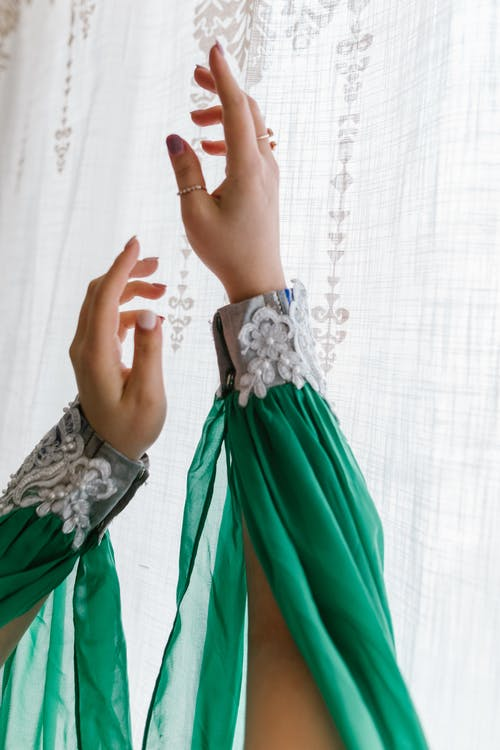Hands Of A Woman in Green and White Sleeves