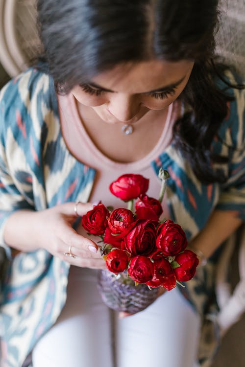 Woman Holding A Bunch Of Red Flowers
