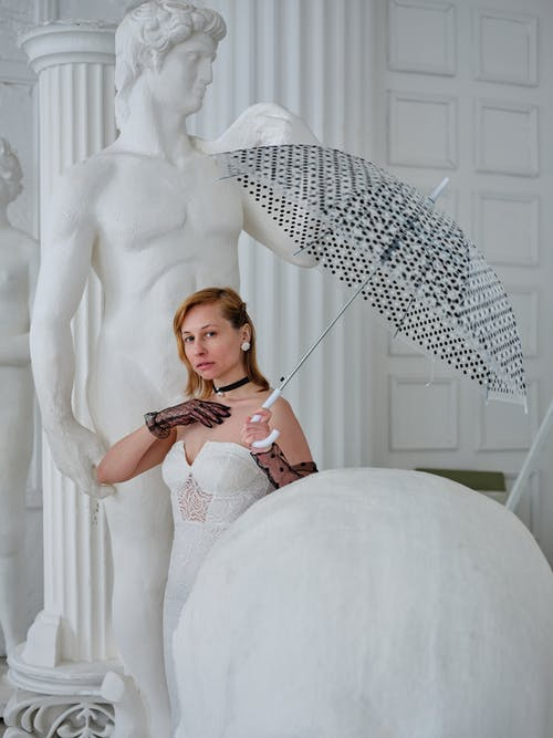 Elegant female with umbrella in gloves looking at camera in antique hall with white statues