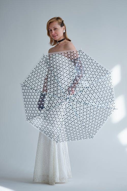 Woman with umbrella in white festive dress