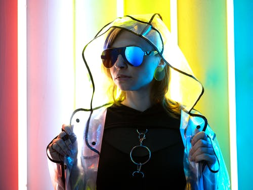 Extravagant young female in trendy unusual clothes looking away near bright glowing neon lights