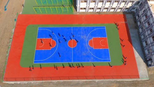 A High Angle Shot of People Playing Football on a Basketball Court