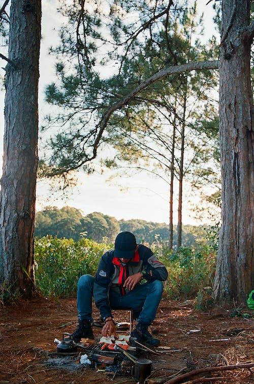 Man in Black Jacket and Blue Denim Jeans Sitting on Brown Tree